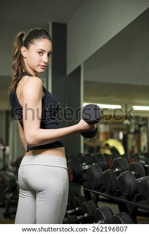 Young 20s woman lifting weights at gym and training looking at the view.Biceps exercises. - stock photo