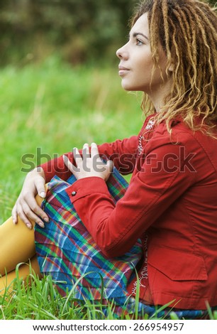 Young sad beautiful woman with dreadlocks in a red dress sits on green grass in park. - stock photo