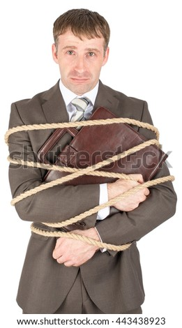 Young sad businessman and briefcase tied with ropes - stock photo