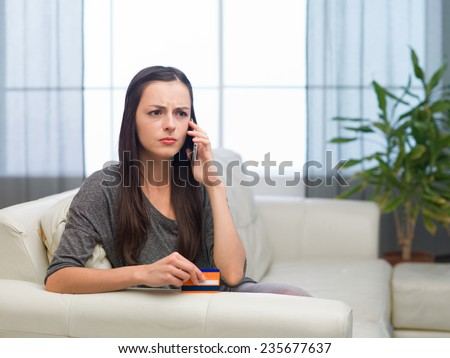young sad caucasian woman holding credit card talking on the phone - stock photo