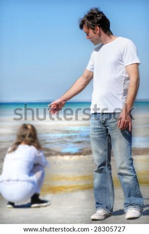 Young sad couple on the beach - stock photo