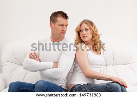 Young sad couple sitting - stock photo
