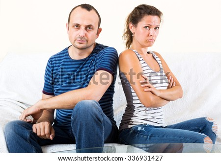 Young sad family sorting out their relationship - stock photo