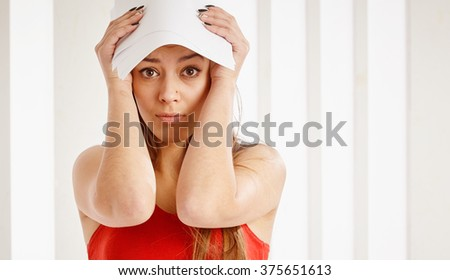 Young sad girl in red top holding papers on her head. - stock photo