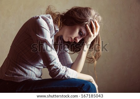 Young sad girl sitting alone in an empty room - stock photo