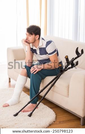 Young sad man is sitting on sofa with broken leg. - stock photo