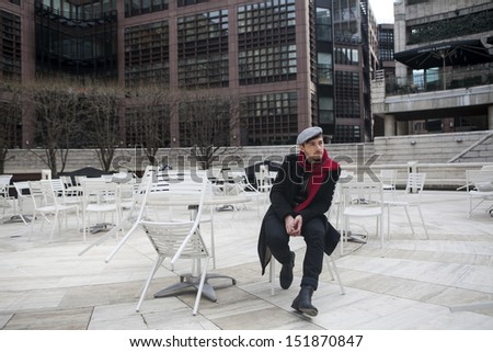 young sad man wearing check cap and red scarf sitting at the street cafe waiting for order - stock photo