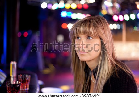 young sad woman in a discotheque - stock photo