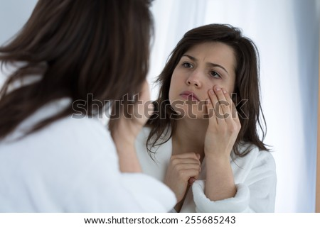 Young sad woman looking in the mirror at her wrinkles - stock photo