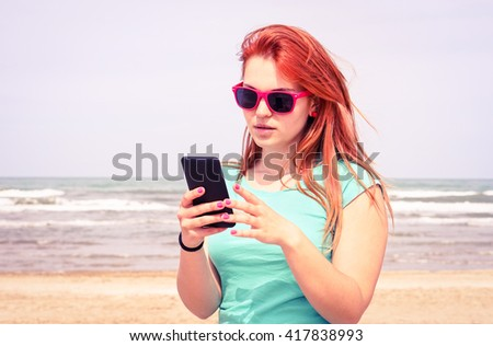 Young sad woman looking mobile phone on the beach - Girl unhappy facial expression reading message on smartphone outdoors - Concept of human bad feelings and internet communication - vintage filter - stock photo