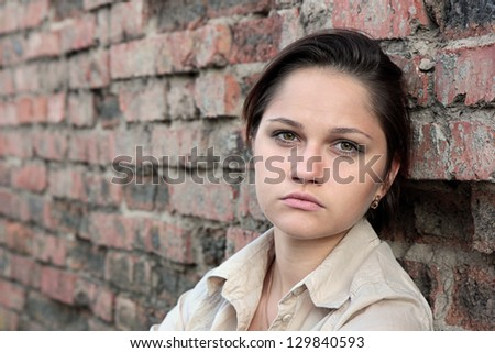 Young sad woman sitting against a brick wall - stock photo