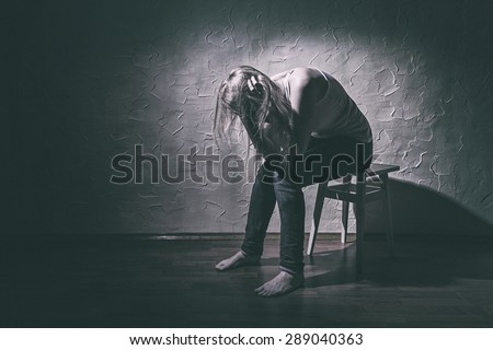 Young sad woman sitting alone in a chair in an empty room - stock photo