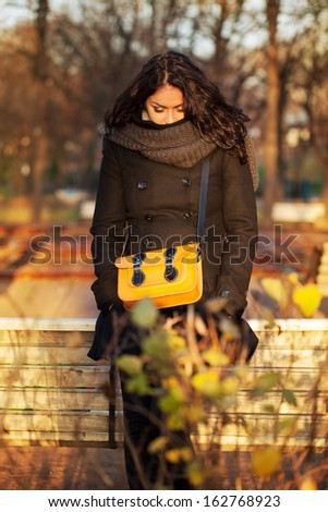Young sad woman stands alone in the park - stock photo