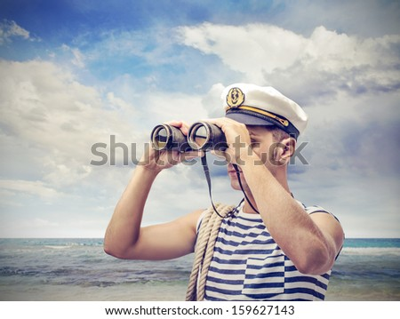 young sailor looks through binoculars - stock photo