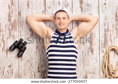 Young sailor lying on deck with a pair of binoculars beside him, smiling and looking at the camera  - stock photo