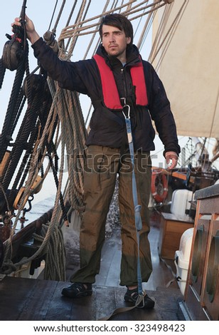 Young sailor onboard with sails behind him - stock photo