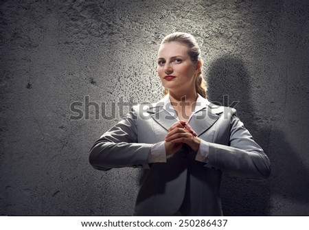 Young saint businesswoman praying with hands on chest - stock photo