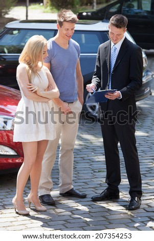 Young salesman showing contract paper to couple by new car - stock photo