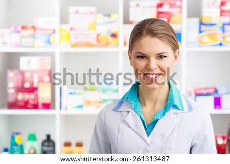Young salesperson in drug store posing over medicines background. Happy smiling woman pharmacist in labcoat servicing customers.   - stock photo