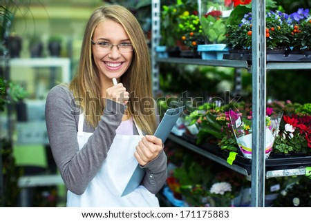 Young saleswoman colors in store - stock photo