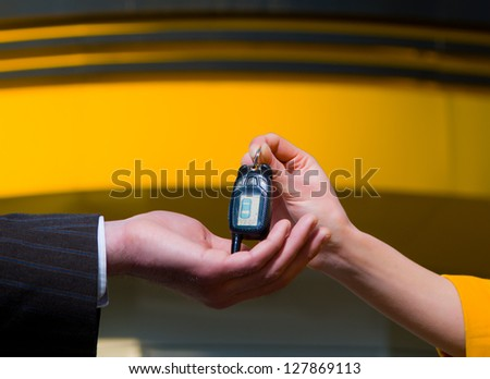 Young saleswoman handing a car key to a customer. - stock photo