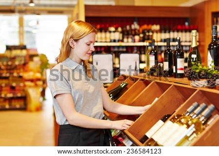 Young saleswoman in supermarket organizing bottles in wine department - stock photo