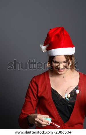 Young santa girl model in front of grey background blowing bubbles - stock photo