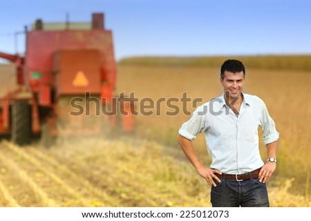 Young satisfied businessman standing on soybean field during harvesting - stock photo