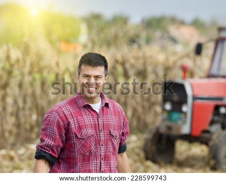 Young satisfied farmer standing in front of agricultural machinery in corn field - stock photo