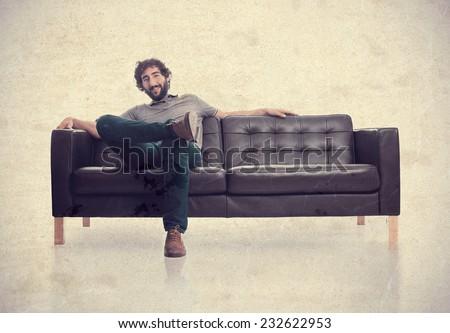 young satisfied man in a sofa - stock photo