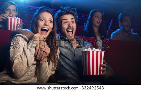 Young scared couple at the cinema watching an horror movie and screaming, she is holding her boyfriend's hand - stock photo