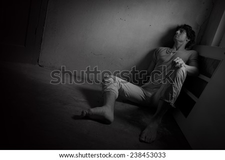 Young scared man experiencing a nightmare - stock photo
