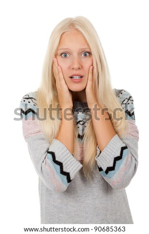 young scared, terrified woman looking at camera holding hand on face, wear winter knitted  sweater, isolated over white background - stock photo