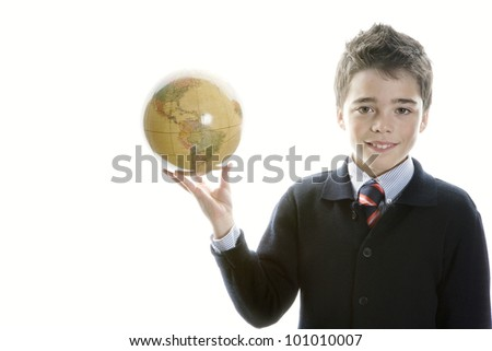 Young school boy holding a globe against a white background smiling and wearing a navy blue school uniform. - stock photo