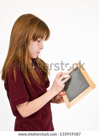 Young school girl writing on chalk board - stock photo