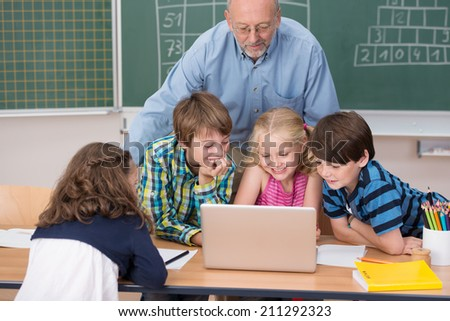 Young school kids in class grouped around a laptop computer on a desk with a male teacher leaning over watching them work - stock photo