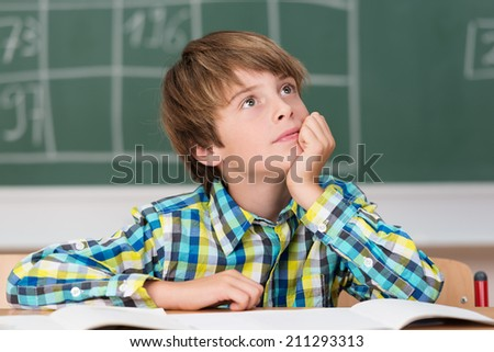 Young schoolboy daydreaming in class as he sits at his desk in front of the blackboard staring thoughtfully up into the air wishing he were playing outdoors - stock photo