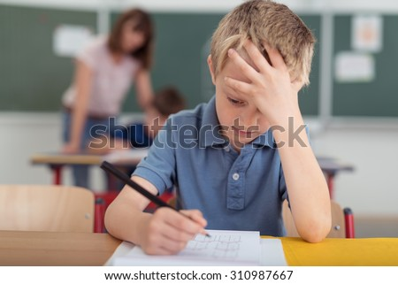 Young schoolboy hard at work in the classroom sitting with his head on his hand reading and writing notes on sheets of white paper - stock photo