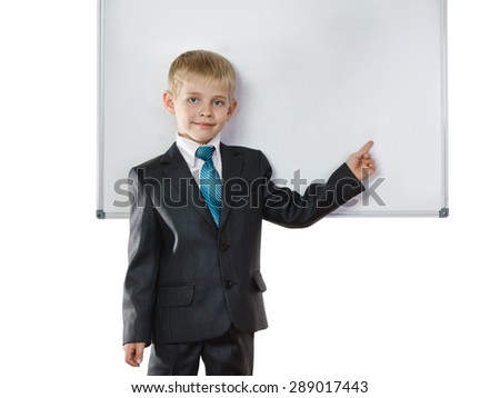 Young schoolboy in suit about blackboard on white background - stock photo
