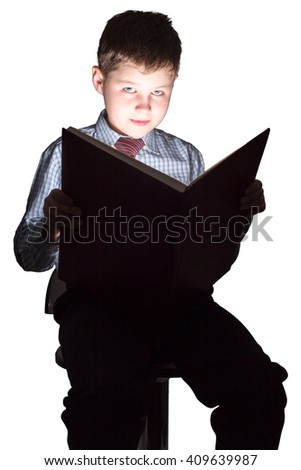 Young schoolboy reading book in the dark - stock photo