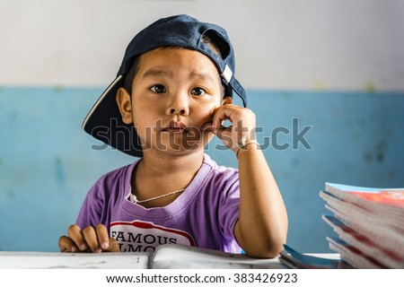 Young schoolboy sitting at his table and looks interested. Thai school in a small village - stock photo