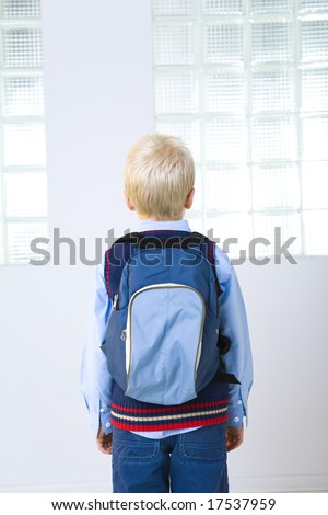Young schoolboy with backpack. He standing back to the camera. Rear view. - stock photo