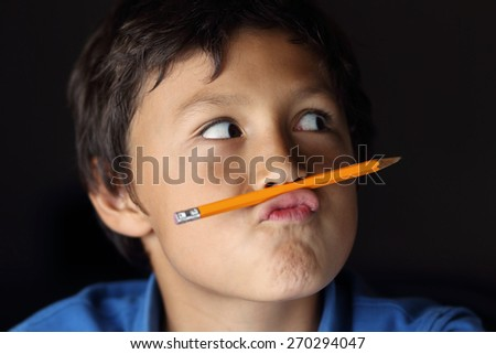 Young schoolboy with pencil - with chiaroscuro lighting - shallow depth of field - stock photo