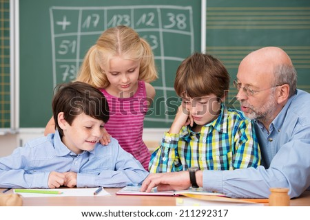 Young schoolchildren in class with their elderly male teacher sitting together at a desk as they discuss a project or class notes - stock photo