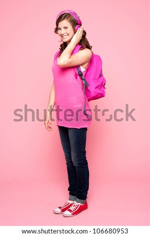 Young schoolgirl enjoying music. Carrying school bag and posing - stock photo