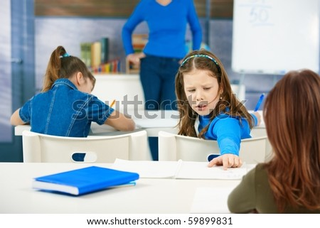 Young schoolgirl peering back at other pupil's work while writing test in class.? - stock photo