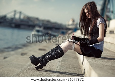 Young schoolgirl sitting on stairs. - stock photo