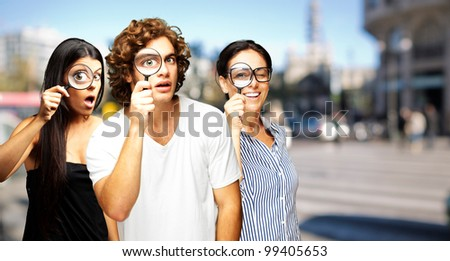 young scientific looking through a magnifying glass at city - stock photo