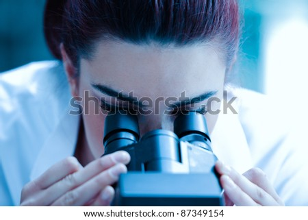 Young scientist looking through a microscope in a laboratory - stock photo