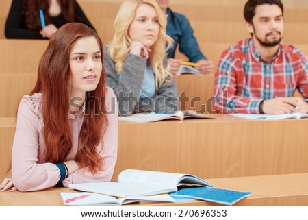 Young scientists. Beautiful female student listening with attention to the teacher at university class while her classmates sitting behind her in blurry - stock photo